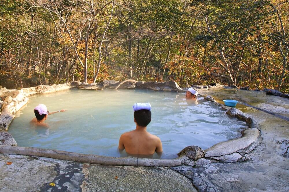 Outdoor onsen people sitting in tub with towels on their heads