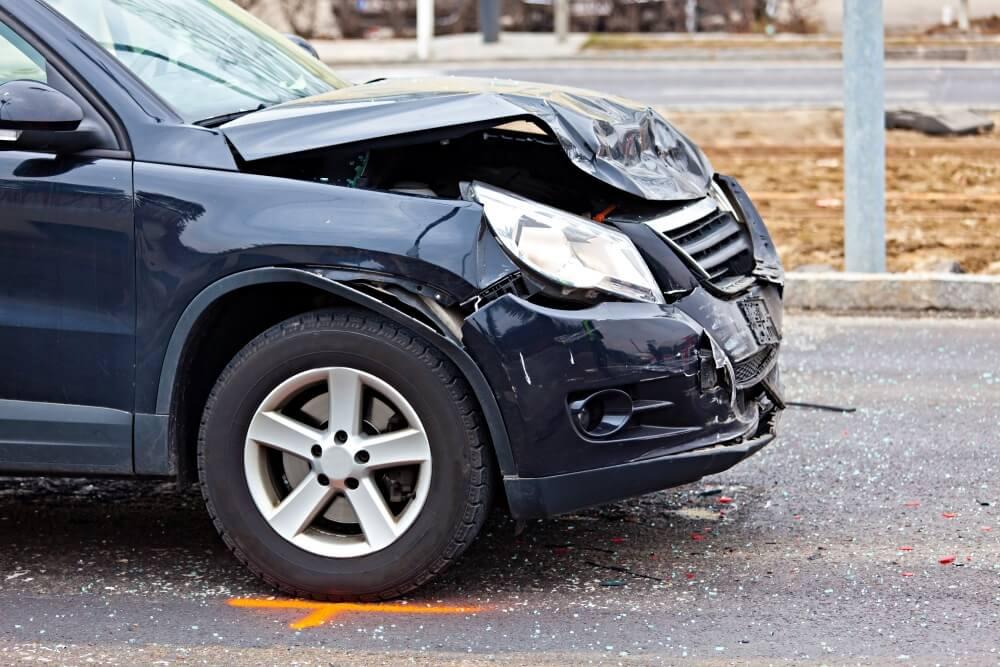 Black car with dent in front can be covered by some travel insurance