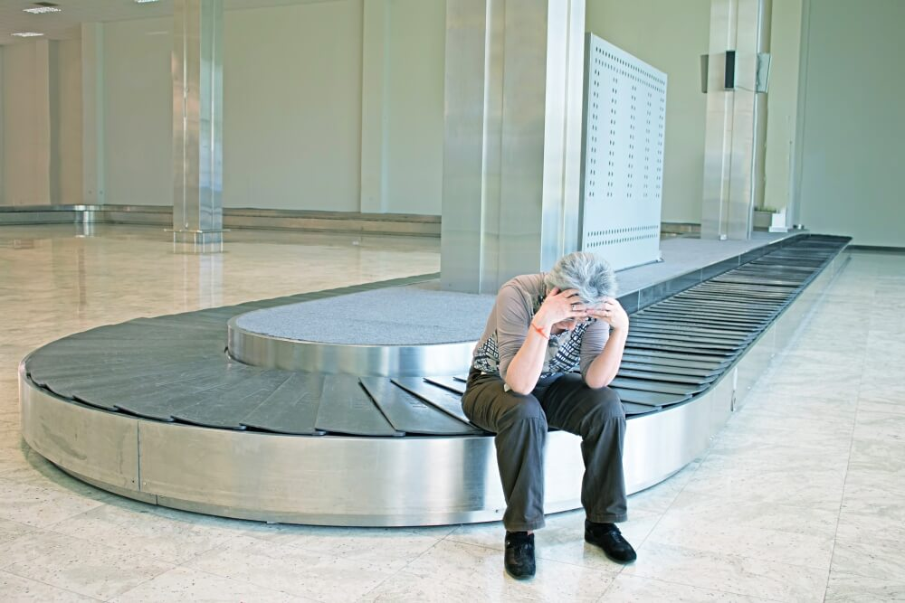 woman sitting at luggage carousel with lost luggage can get money form her travel insurarnce
