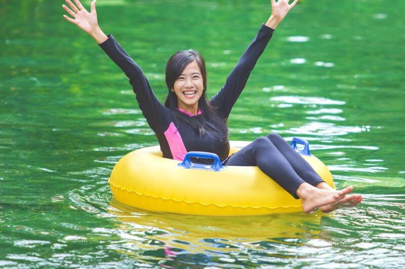 woman smiling while river tubing in the blue ridge mountains